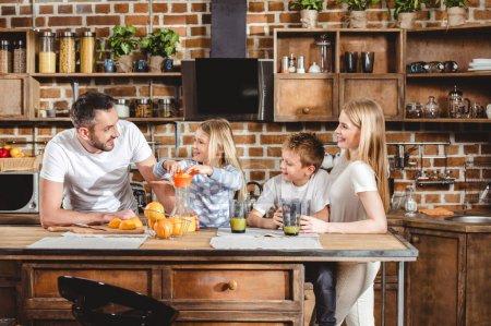 Photo pour Heureuse famille de quatre fait du jus d'orange pour le petit déjeuner dans la cuisine - image libre de droit