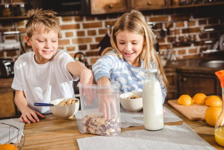 Photo for Brother and sister have corn flake rings for breakfast sitting at the table in kitchen - Royalty Free Image