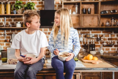 Photo for Brother and sister have breakfast sitting on the table in kitchen - Royalty Free Image