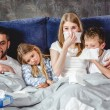 Family of four has a flue and lying on bed togethe...