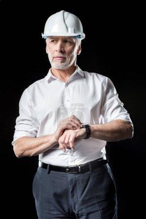 Photo pour Mature architecte masculin en blanc dur chapeau vérifier montre-bracelet isolé sur noir - image libre de droit