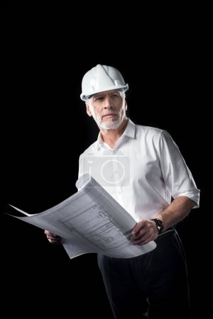 Photo pour Mature male architect in white hard hat holding blueprints and looking away  isolated on black - image libre de droit