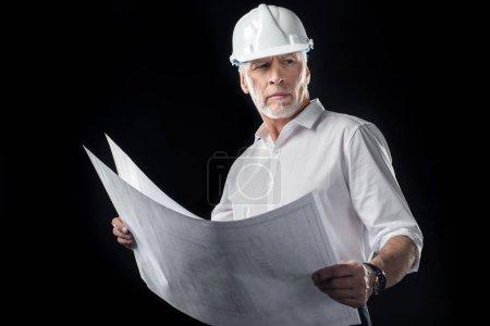 Photo pour Mature architecte masculin en chapeau dur blanc tenant des plans et regardant loin isolé sur noir - image libre de droit