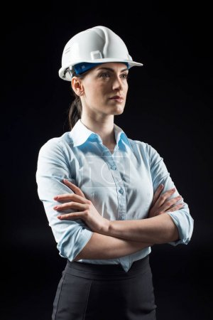 Foto de Female architect in helmet standing with arms crossed and looking at distance isolated on black - Imagen libre de derechos