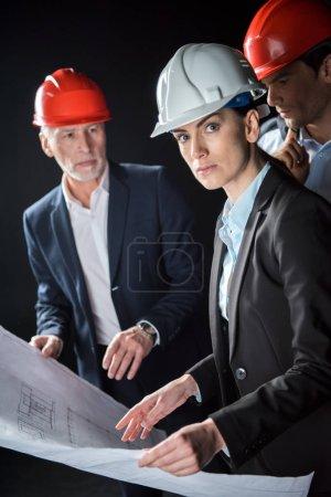 Photo pour Groupe d'architectes professionnels masculins et féminins discutant du plan isolé sur noir - image libre de droit