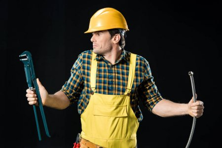 Confused foreman holding pipe wrench