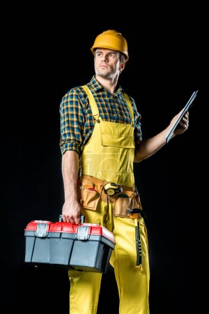 Photo for Pensive workman holding tool kit and clipboard  isolated on black - Royalty Free Image