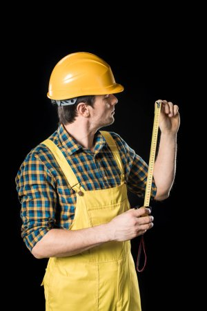 Photo for Workman in yellow hard hat holding meter roller  isolated on black - Royalty Free Image