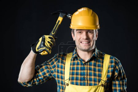 Photo pour Male worker holding hammer on his hard hat and smiling white looking at camera isolated on black - image libre de droit