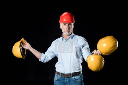 Man holding hard hats