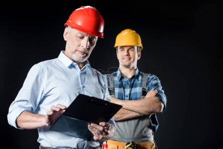 Photo for Portrait of workman and architect with clipboard on black - Royalty Free Image