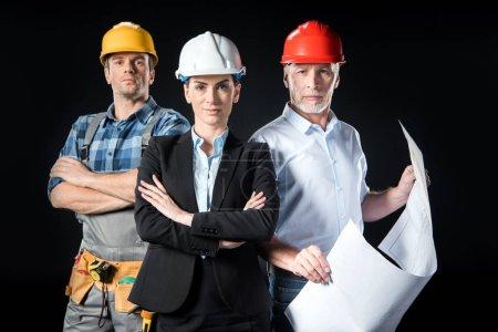 Photo pour Portrait de deux architectes confiants et ingénieur en casques sur fond noir - image libre de droit