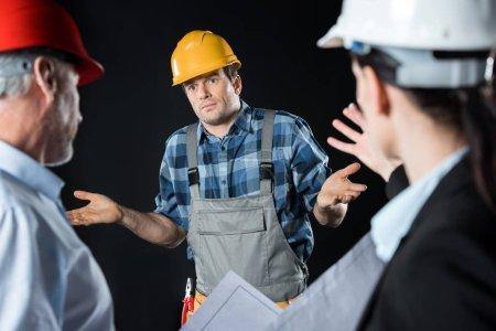 Photo pour Deux architectes en colère blâmant ingénieur en casque dur sur noir - image libre de droit