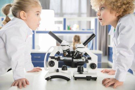 Photo pour Écoliers en blouse de laboratoire utilisant des microscopes et se regardant en laboratoire - image libre de droit