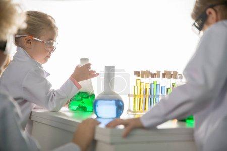 Photo pour Écoliers faisant des expériences avec des éprouvettes et des flacons en laboratoire chimique - image libre de droit