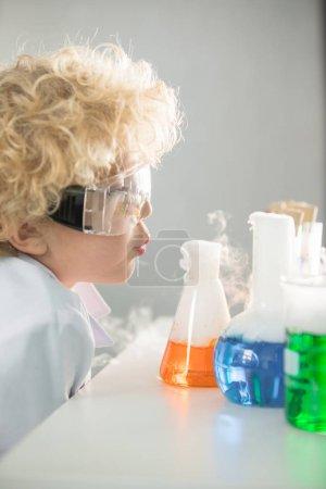 Schoolboy looking at flasks