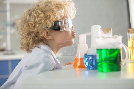 Photo pour Écolier bouclé en lunettes de protection regardant des flacons et des tubes - image libre de droit