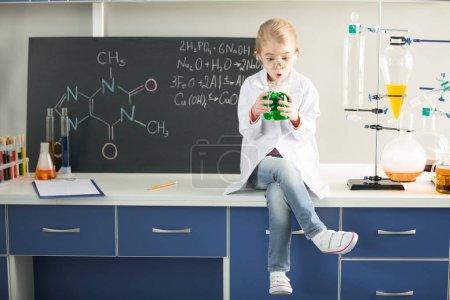 Photo pour Écolière tenant la fiole avec un échantillon chimique tout en étant assis dans le laboratoire - image libre de droit