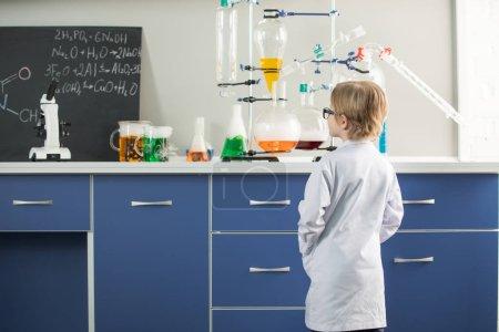Photo pour Vue arrière du petit garçon portant blouse de laboratoire au laboratoire des sciences - image libre de droit