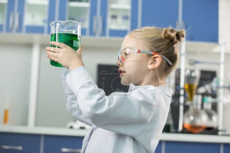 Photo for Little girl wearing lab coat and protective glasses holding flask with green reagent - Royalty Free Image