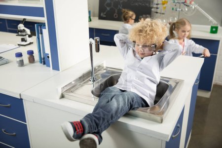 Boy sitting in sink