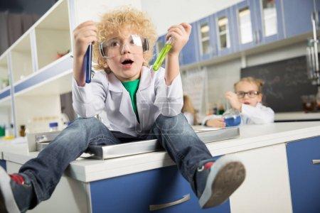 Photo pour Petit garçon assis dans l'évier dans un laboratoire scientifique et tenant des éprouvettes avec des réactifs - image libre de droit