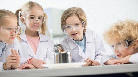 Photo pour Quatre enfants portant des lunettes de protection en laboratoire scientifique - image libre de droit