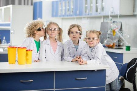 Photo pour Quatre enfants en laboratoire de science portant des manteaux et debout à la table - image libre de droit