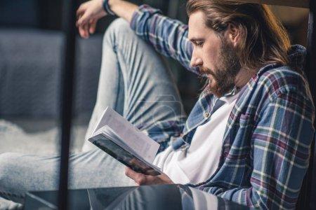 Photo pour Jeune homme barbu assis sur le tapis et le livre de lecture - image libre de droit