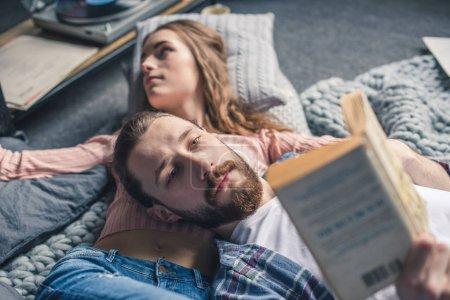 Photo pour Beau jeune couple couché sur couverture tricotée et livre de lecture - image libre de droit