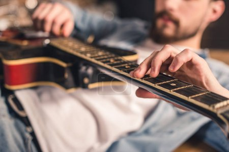 Photo for Close up partial view of young man playing guitar - Royalty Free Image