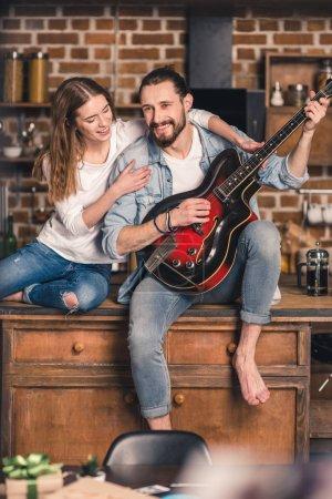 Photo pour Jeune homme jouant la chanson à la guitare pour sa superbe copine - image libre de droit