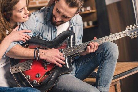 Photo pour Jeune homme jouant la chanson à la guitare pour sa belle petite amie - image libre de droit
