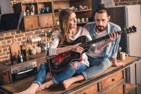 Photo pour Beutiful jeune femme jouant la chanson à la guitare pour son copain - image libre de droit