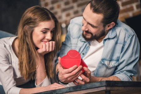 Photo for Young man gives gift in heart shaped box to his beautiful girlfriend - Royalty Free Image