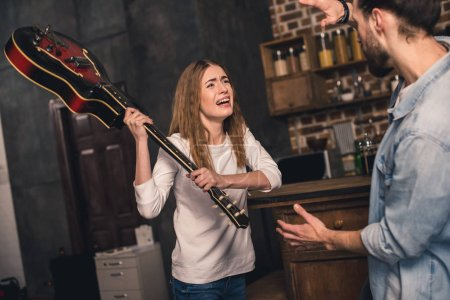 Photo for Young angry woman trying to hit a man with guitar in the kitchen - Royalty Free Image