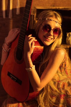 Photo for Young smiling woman in boho style and sunglasses posing with guitar - Royalty Free Image