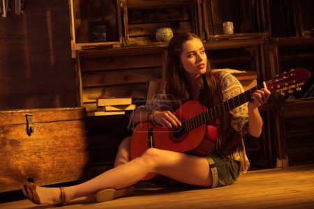 woman in boho style playing guitar