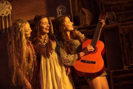 bohemian women playing guitar