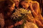 Women in boho style smelling flowers