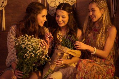 Foto de Tres jóvenes sonrientes en estilo boho posando con ramos de flores - Imagen libre de derechos