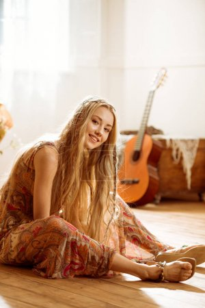 Foto de Smiling young woman in boho style sitting on floor and looking at camera - Imagen libre de derechos