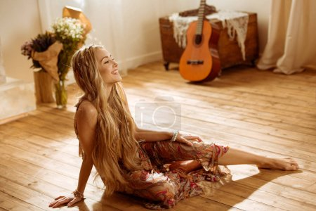 Foto de Smiling young woman with long hair woman in bohemian style sitting on wooden floor - Imagen libre de derechos