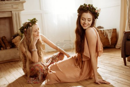 Photo for Smiling young bohemian women in floral wreaths sitting on floor - Royalty Free Image
