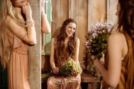 Young bohemian women holding flowers