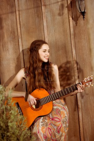 Young bohemian woman playing guitar