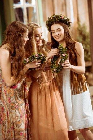Photo pour Trois jeunes femmes magnifiques heureuses dans le modèle de boho retenant des couronnes florales - image libre de droit