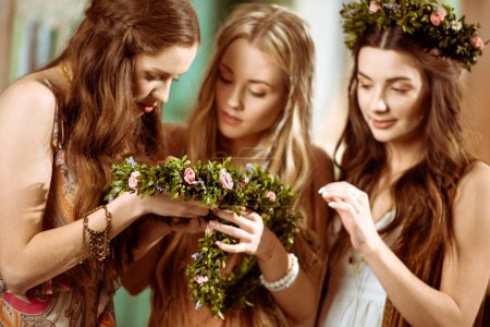 Photo pour Trois jeunes femmes magnifiques dans le style bohème tenant des couronnes florales - image libre de droit