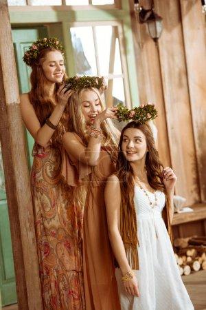 Photo pour Trois femmes dans le style bohème portant des couronnes florales tout en se tenant dans la rangée - image libre de droit