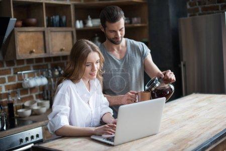 Photo pour Souriant jeune couple boire du café tout en utilisant un ordinateur portable dans la cuisine - image libre de droit